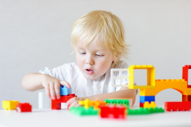 Cute toddler boy playing with colorful plastic blocks indoors