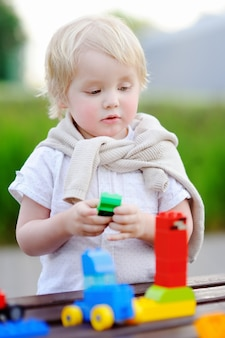 Cute toddler boy playing with toy train and colorful plastic blocks outdoors at warm day