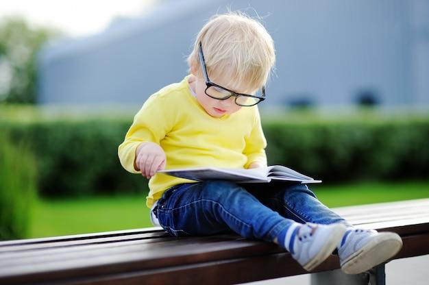 暖かい夏の日に屋外で本を読んでかわいい幼児男の子。学校のコンセプトに戻る