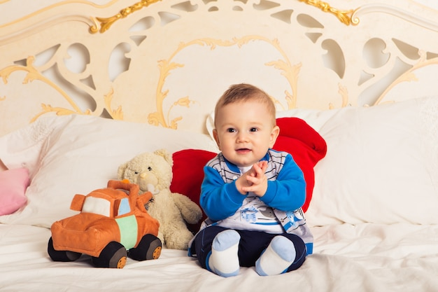 Cute toddler boy sitting on the bed and playing with a toy. early learning for kids. activities with children at home.