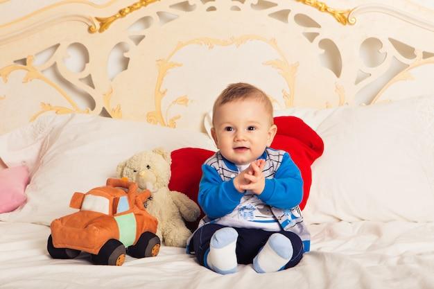 ベッドの上に座っておもちゃで遊ぶかわいい幼児の少年。子供のための早期学習。自宅で子供たちとの活動。