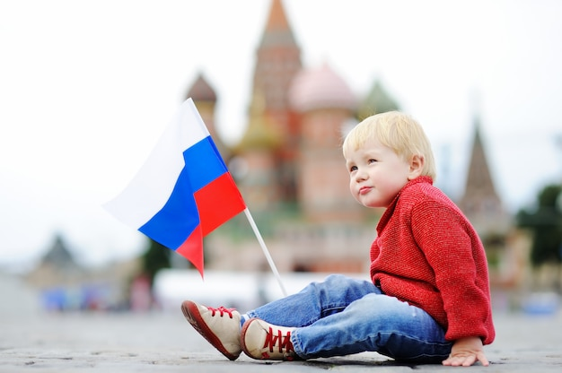 Cute toddler boy sitting and playing with russian flag with red square and vasilevsky descent