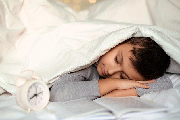 Cute toddler boy sleeping with a book under a white blanket.