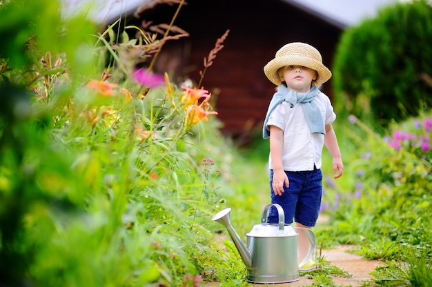 Cute toddler boy in straw hat watering plants in the garden at summer sunny day