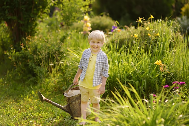 Cute toddler boy watering plants in the garden at summer sunny day.
