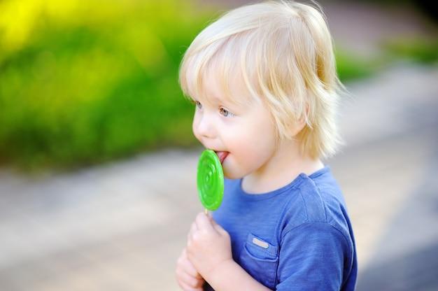 大きな緑のロリポップとかわいい幼児男の子。甘いお菓子バーを食べる子。幼児向けのお菓子。夏のアウトドアの楽しみ