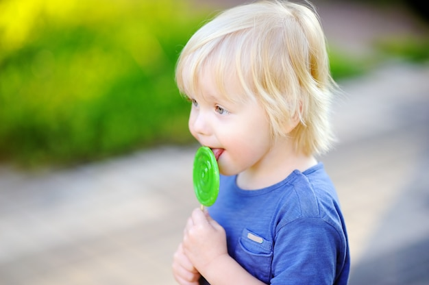 Cute toddler boy with big green lollipop. child eating sweet candy bar. sweets for young kids. summer outdoor fun