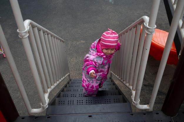 Милый малыш поднимается по лестнице на детскую площадку, вид сверху