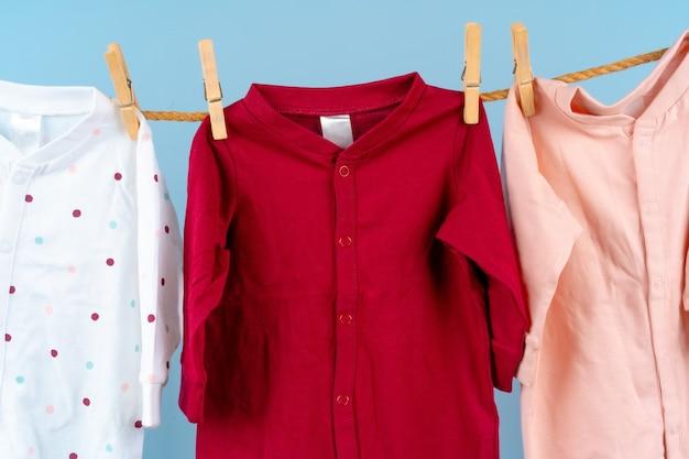 귀여운 유아 다채로운 옷이 밧줄에 매달려