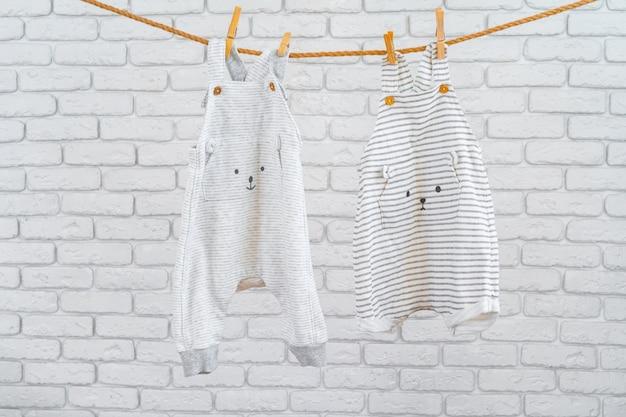 かわいい幼児のカラフルな服をロープに掛ける