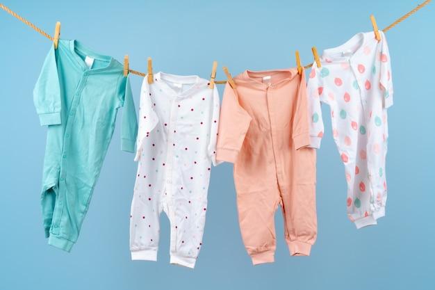 かわいい幼児のカラフルな服がロープにぶら下がる