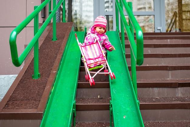귀여운 유아가 계단 경사로를 따라 장난감 유모차를 끌고 있습니다. 장애인용 경사로, 유모차 밀기, 넘어지지 않도록 스테인리스 막대가 있는 카트