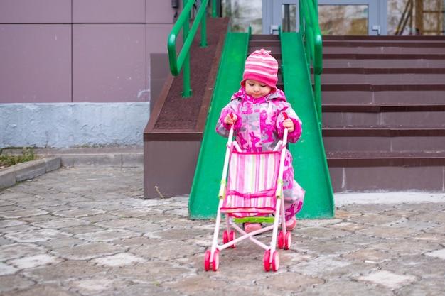 귀여운 유아는 장애인을 위한 계단 경사로를 따라 장난감 유모차를 끌고 있습니다.