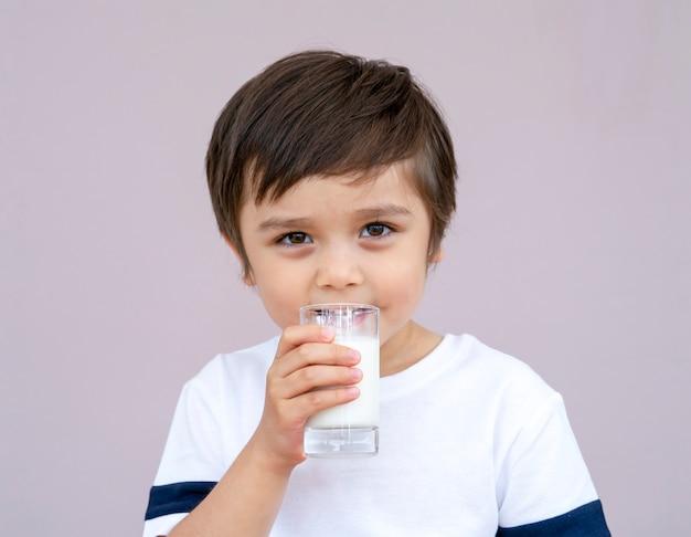 Милый малыш пьет свежее молоко из стакана