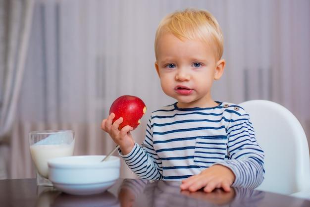 かわいい幼児が食事を食べ、リンゴを手に持って、笑顔で。