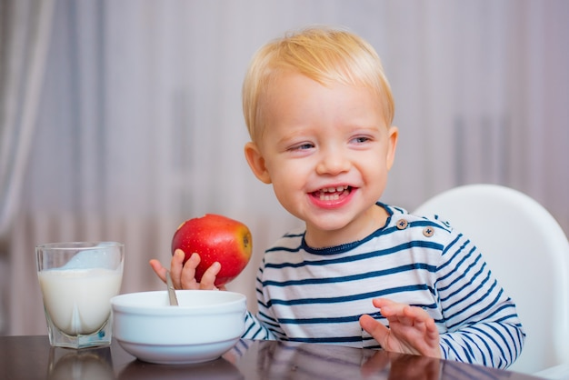 Cute toddler eating his meal, holding an apple in his hand, smiling.