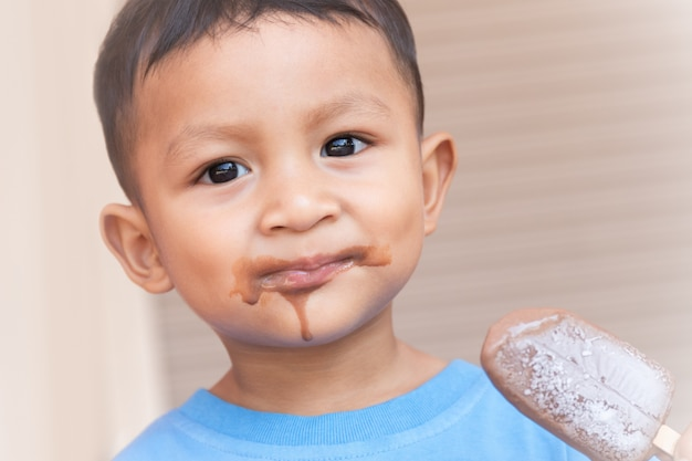 Cute toddler eating ice cream with his mouth dirty