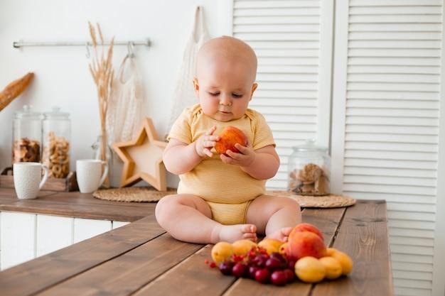 かわいい幼児が自宅の木製キッチンで果物を食べる