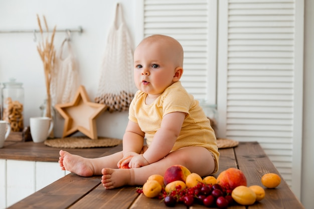 Cute toddler eats fruit in wooden kitchen at home