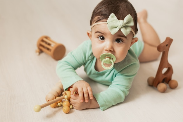 Cute toddler girl of 8 months lies on wooden floor of house playing with wooden development toys. high quality photo