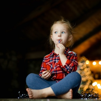 Cute toddler girl eating chocolate egg sitting in a hunting house decorated for christmas.