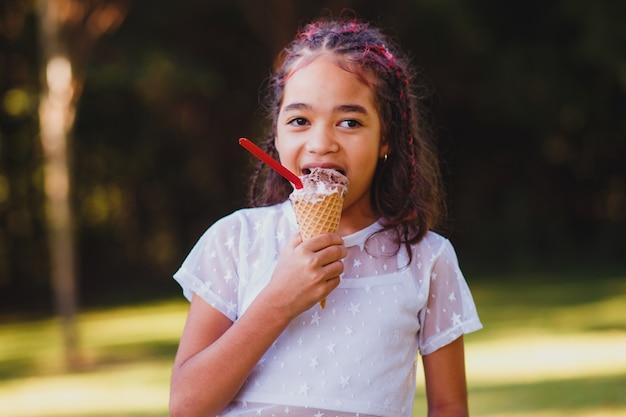 Милая девочка малыша ест мороженое