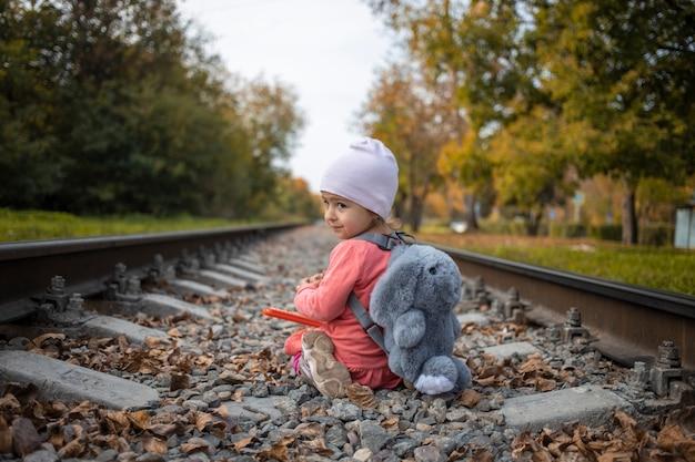 귀여운 어린 소녀가 화창한 여름날, 위험한 상황에서 혼자 철도에서 놀고 있습니다.