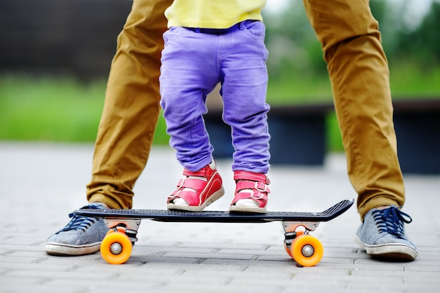 Cute toddler girl learning to skateboard with her father close up outdoors. active family fun