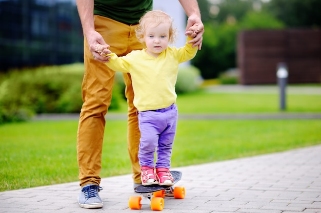 Cute toddler girl learning to skateboard with her father outdoors