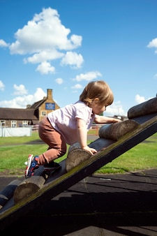 Cute toddler girl at a playground, climbing on the wooden stairs. education and parenting concept