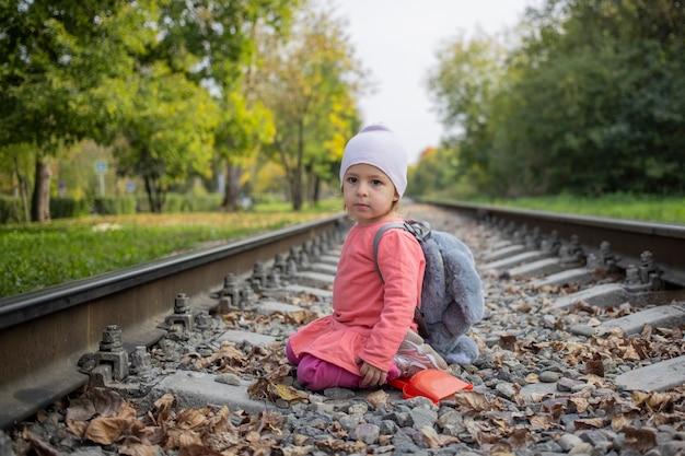철도 제방에서 돌을 가지고 노는 귀여운 유아 소녀. 위험한 게임