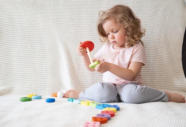 ソファに座って木のおもちゃで遊ぶかわいい幼児の女の子。