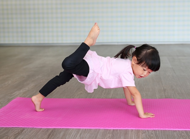 Cute toddler girl practicing yoga
