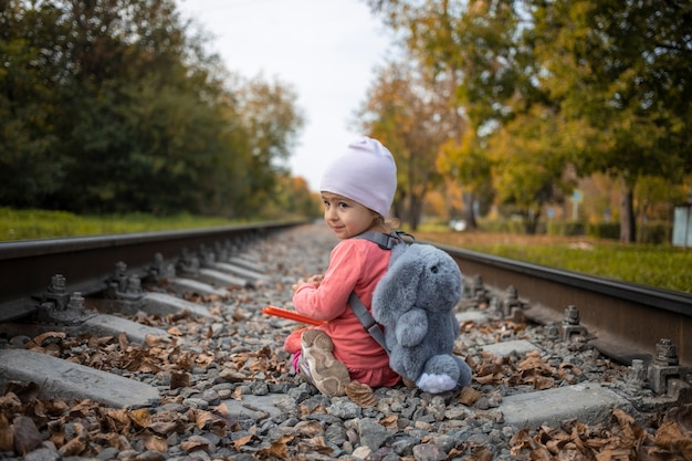 귀여운 어린 소녀는 위험한 상황에서 여름날 혼자 철도에 앉아 있습니다.