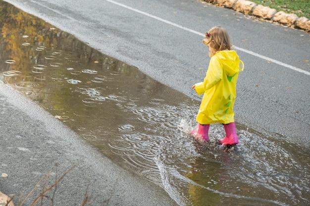 Милая девочка малыша носить желтый стильный плащ розовые резиновые сапоги бегает в луже.