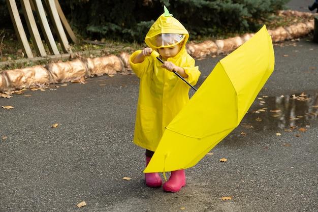 Милая девочка малыша носить желтый стильный плащ розовые резиновые сапоги, стоя с зонтиком.