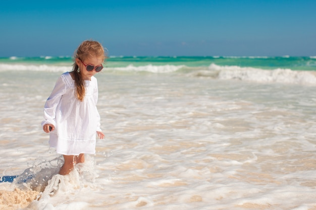 Cute toddler girl in white dress standing in shallow water at exotic beach