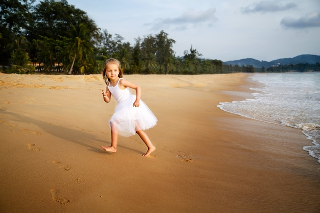 Cute toddler girl with blonde hair in a white tutu dress running on a sandy beach at sunset.