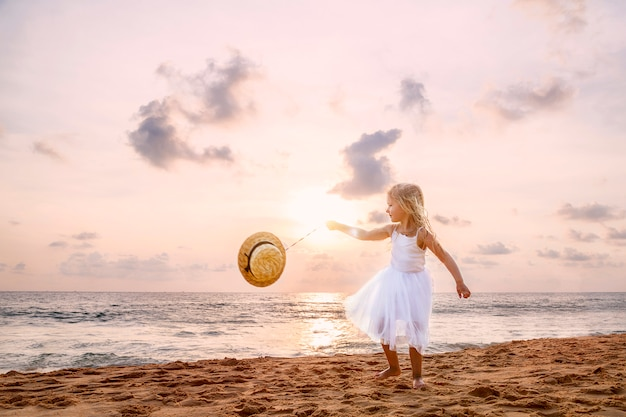 Cute toddler girl with blonde hair in a white tutu dress walking on a sandy beach at sunset.