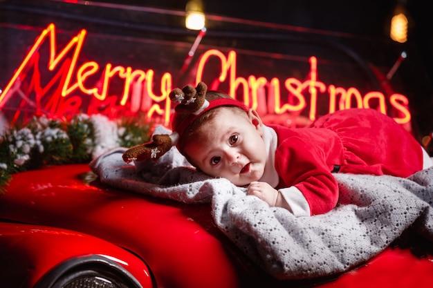 Милая девочка малыша с рогами оленя позирует в рождественской студии. скопируйте пространство. жениться на рождестве на фоне.