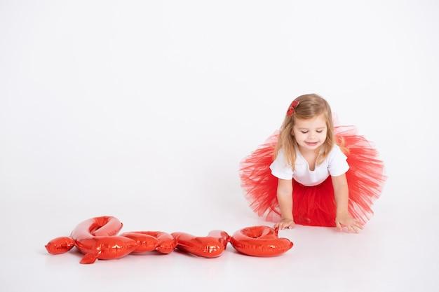 白い背景の上の風船からの碑文の愛を持つかわいい幼児の女の子。バレンタイン・デー。