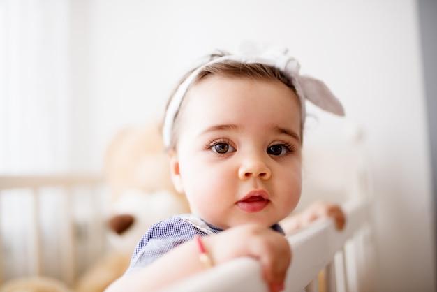 그녀의 침대에서 귀여운 유아입니다. 그녀의 테디 베어와 함께 편안한 순간.