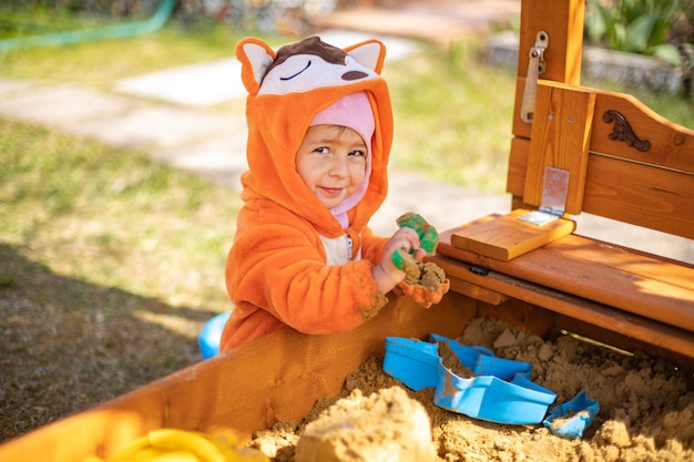 주황색 점프수트를 입은 귀여운 유아는 화창한 날 야외 샌드박스에서 모래에서 놀고 있습니다.