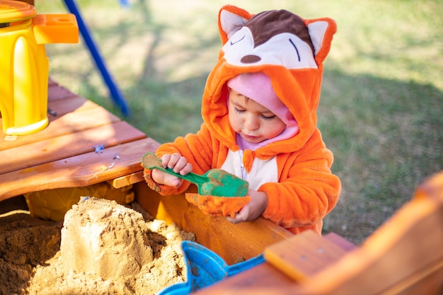 주황색 점프수트를 입은 귀여운 유아는 화창한 날 야외 샌드박스의 모래에서 놀고 있다