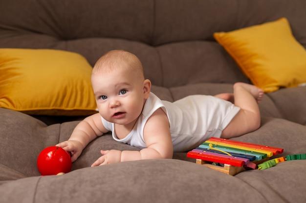흰색 바디 슈트에 귀여운 유아는 나무 개발 장난감을 가지고 노는 노란색 베개와 회색 소파에 집에 놓여 있습니다