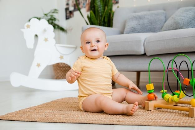 黄色のボディスーツを着たかわいい幼児が、開発中のおもちゃで遊んで床に家に座っています。子どもの発達の概念