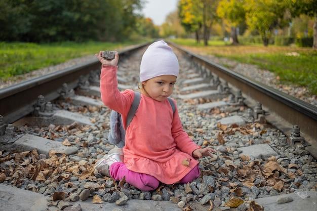 철도 제방 위험한 게임에서 돌을 가지고 노는 귀여운 유아