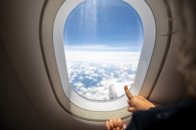 Cute toddler points his finger at the sky through the window. first flight concept, traveling with children.