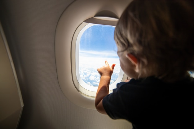 Cute toddler points his finger at the sky through the window first flight concept traveling with