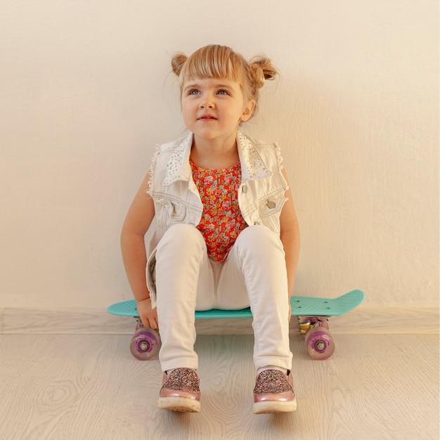 Cute toddler posing on skateboard
